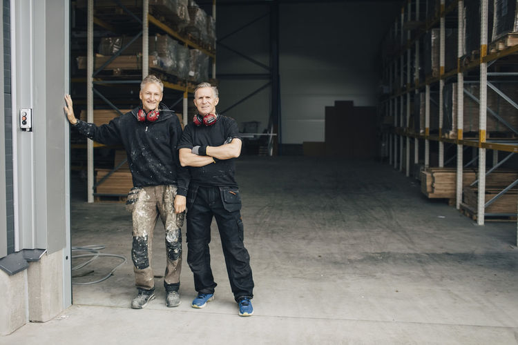 Full length portrait of confident workers standing in entrance at industry