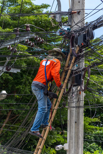 Cable Complexity Connection Day Electricity  Electricity Pylon Fuel And Power Generation Full Length Helmet Low Angle View Maintenance Engineer Manual Worker Men Occupation One Person Only Men Outdoors Power Line  Power Supply Rear View Reflective Clothing Repairing Repairman Telephone Line Working