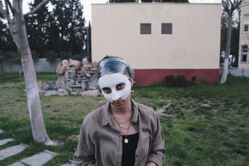 Portrait of woman with facial mask standing in back yard