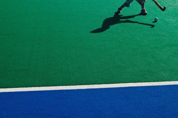 Low section of man playing hockey on field