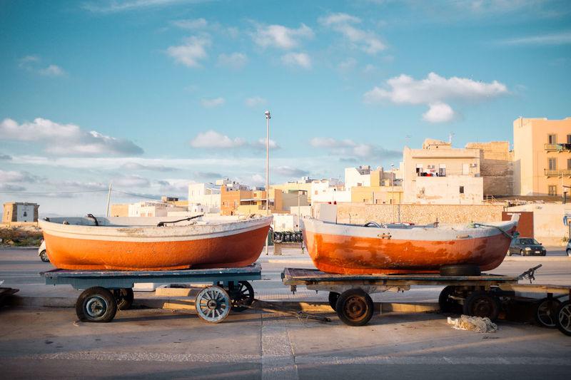 Orange boats on cart against buildings