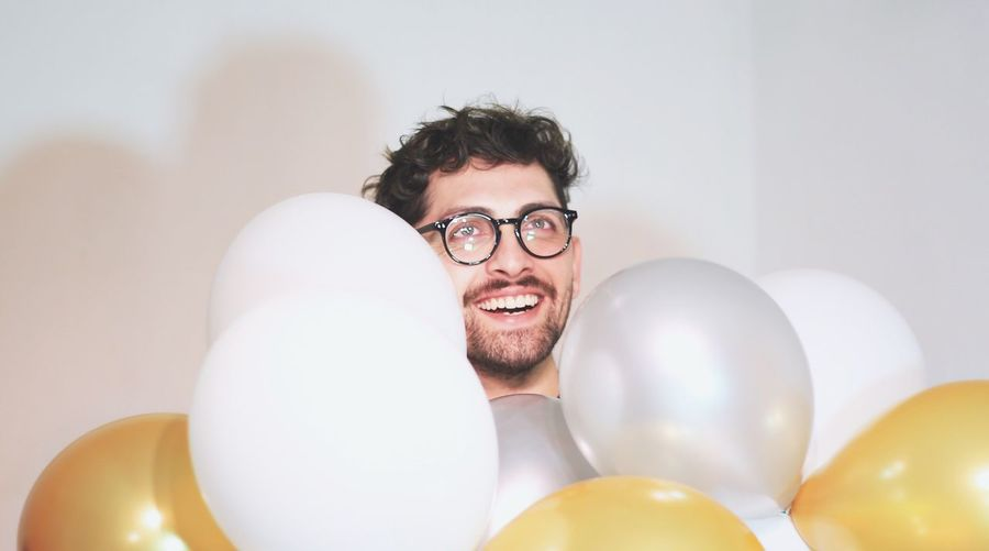 Portrait of smiling young man with balloons