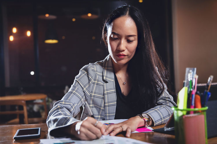 Businesswoman writing on document while sitting in office