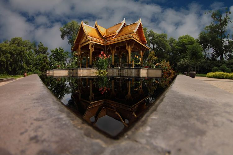 Surface level shot of temple reflecting in pond
