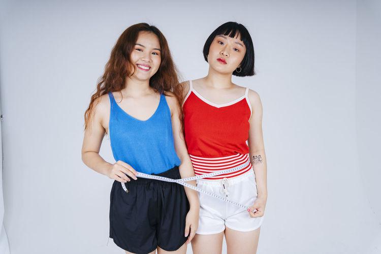 Portrait of lesbian couple measuring waist against gray background