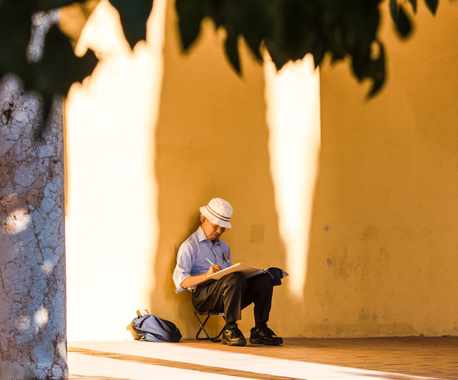 Artist Man With Hat Mezquita Mezquita De Córdoba Paint The Town Yellow The Week On EyeEm Bag Casual Clothing Day Full Length Leaves Lifestyles Light And Shadow Nature One Person Outdoors Painter People Real People Relaxation Sitting Tree Yellow Color Young Adult