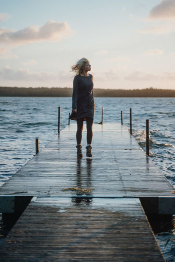 Woman standing on jetty during storm Water Sky Wood - Material Pier Rear View Leisure Activity Beauty In Nature One Person Nature Cloud - Sky Women Lifestyles Jetty Real People Standing Scenics - Nature Lake Day Post Outdoors Pier Rough Nordic Scandinavian Holiday Moments My Best Photo