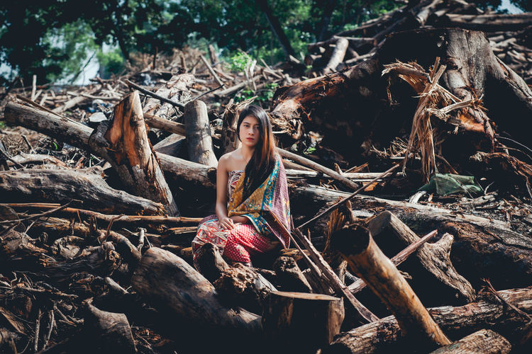 Sad native girl. Her surrounding jungle destroyed by logging activities. Beautiful Woman Day Dead Plant Forest Front View Full Length Hairstyle Land Leisure Activity Lifestyles Log Nature One Person Outdoors Plant Portrait Real People Sitting Tree Women Wood Wood - Material WoodLand Young Adult Young Women The Photojournalist - 2018 EyeEm Awards The Portraitist - 2018 EyeEm Awards
