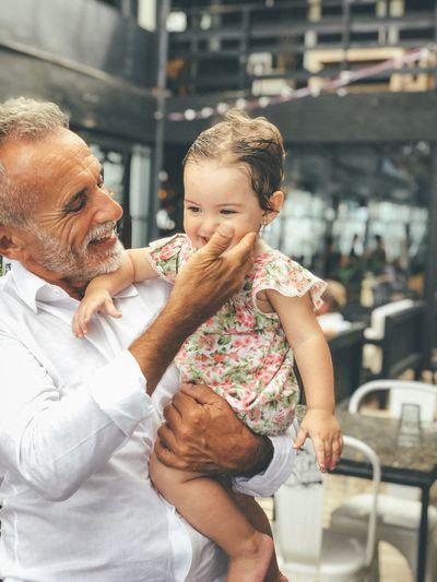 Smiling senior man carrying granddaughter
