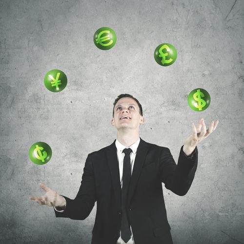 Digital Composite Image Of Businessman Juggling Financial Symbols Against Wall
