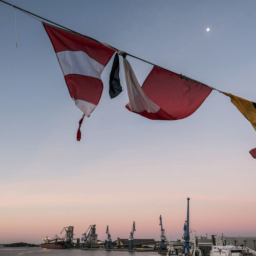 Low angle view of flags against sky during sunset