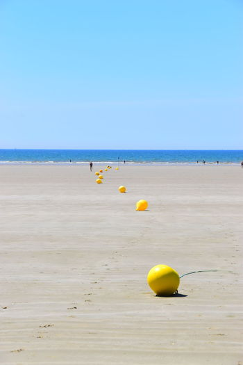 Yellow floating on sea against clear sky