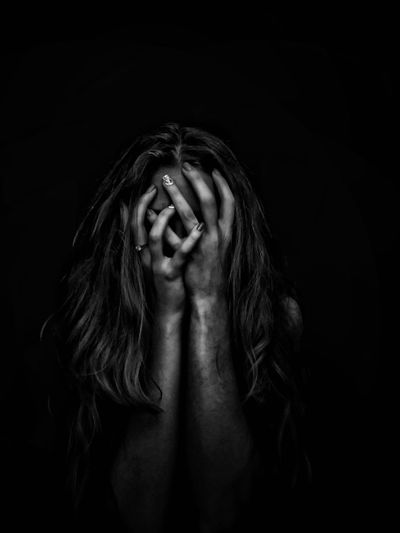 Close-up of woman covering face with hands over black background
