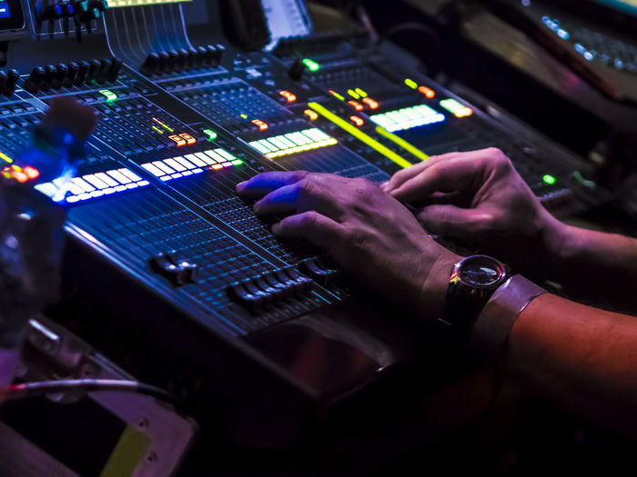 Cropped hands of male dj using control panel during music concert