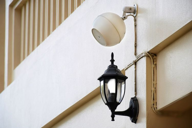 Low angle view of lamp hanging on wall