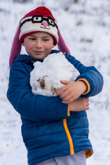 Cute boy holding snow during winter