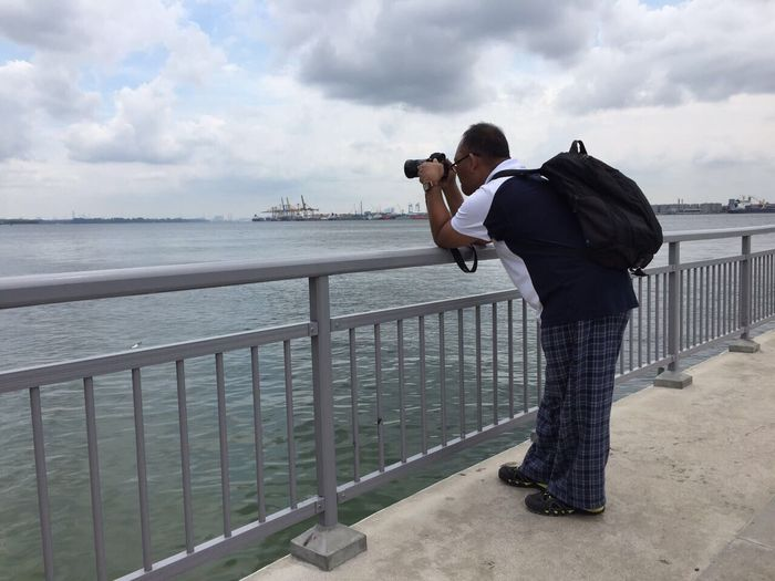 Full length of man photographing through camera while standing on bridge over sea