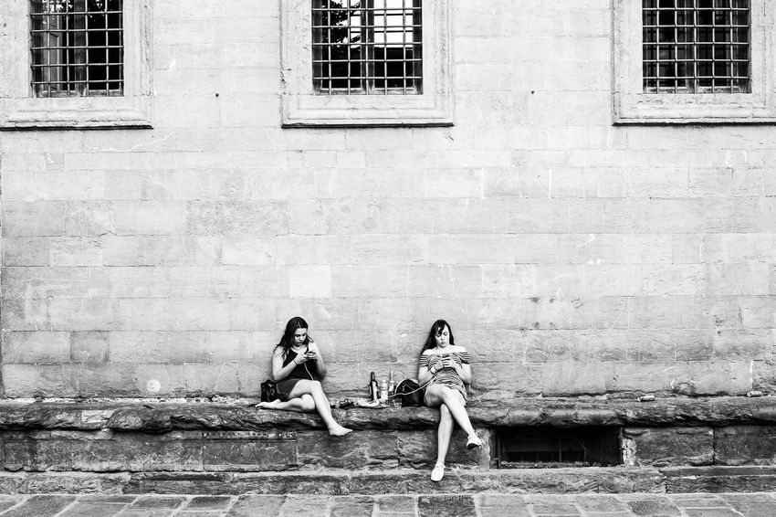 street photo of two young women sitting at an old building in Ghent, Belgium Architecture Belgium Black And White Building Exterior Built Structure City Day Friendship Gent Ghent Old Building  Outdoors Phone Real People Relaxation Street Street Photography Streetphoto_bw Streetphotography Togetherness Two People Women Young Adult Young Women