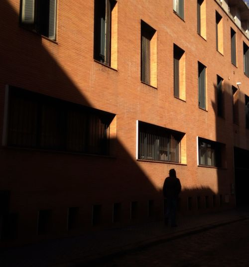 Silhouette of man in front of building