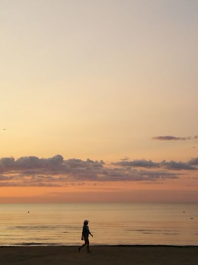 Woman walking at beach against sky during sunset