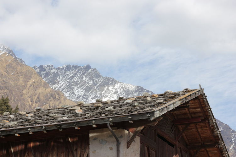 Low angle view of hut by mountains against sky