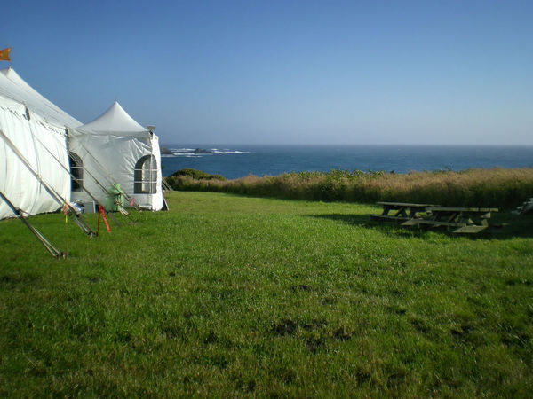 White festival tent on green grass, overlooking the blue Pacific Ocean, under a clear blue sky California Coast Event Festival Season Mendocino County Ocean View Blue Sky Clear Sky Day Entertainment Festival Field Grass Green Color Horizon Horizon Over Water Land Mendocino Coast No People Sea Sky Summer Summer Festival Tranquil Scene Tranquility Water