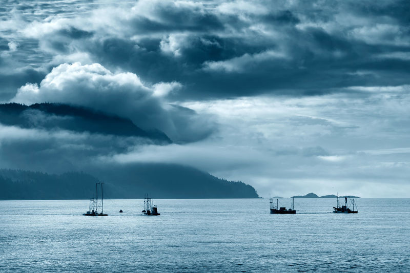 Silhouette Boats Reefnet Fishing Amidst Sea Against Cloudy Sky