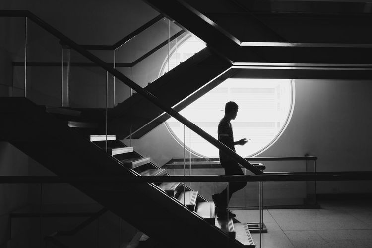 Silhouette photo of a man holding a mobile phone walking down the stairs. Staircase Silhouette Steps And Staircases Real People Indoors  Steps One Person Architecture Modern People Blackandwhite Built Structure