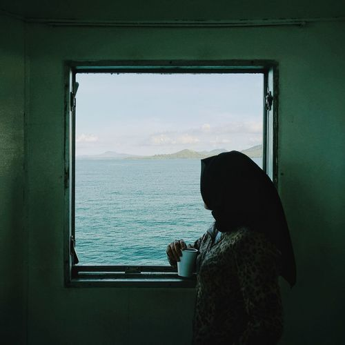 Side View Of Woman In Hijab Having Drink While Looking At Sea Through Window