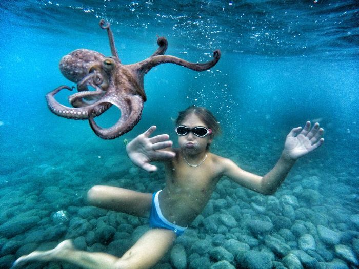Shirtless boy touching octopus while swimming undersea