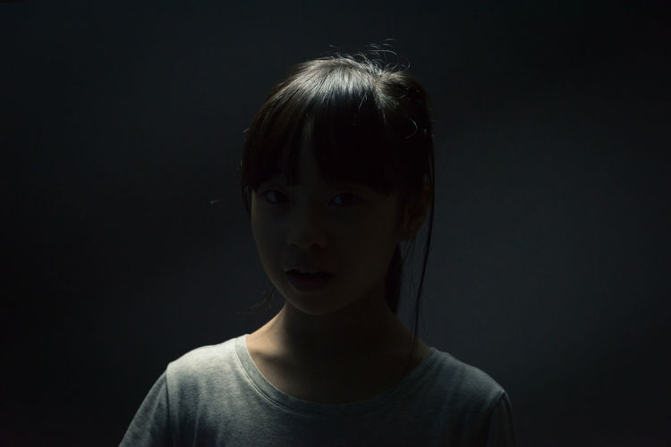 An asian girl under dark environment Anonymous Asian  Back Light Black Background Evil Ghost Tragic  Abuse Back Lighting Bully Bullying Creapy Dark Side Girl Girls Light And Shadow Mysterious One Person Portrait Secret Shadow Smile Studio Shot Unfortunate Unfortunately