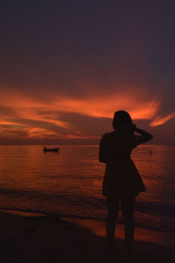 Rear view of silhouette woman standing on beach during sunset