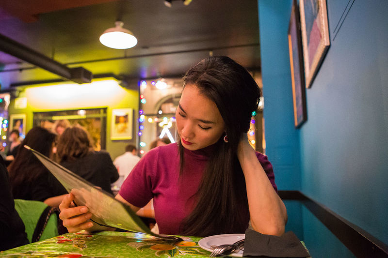 EyeEm Best Shots Eye Em Best Shots Real People Dining Out Dinner City Life Restaurant Scene Restaurant Portrait Of A Woman Women Who Inspire You Primary Colors Reading Menu Menu Date Night Let Your Hair Down