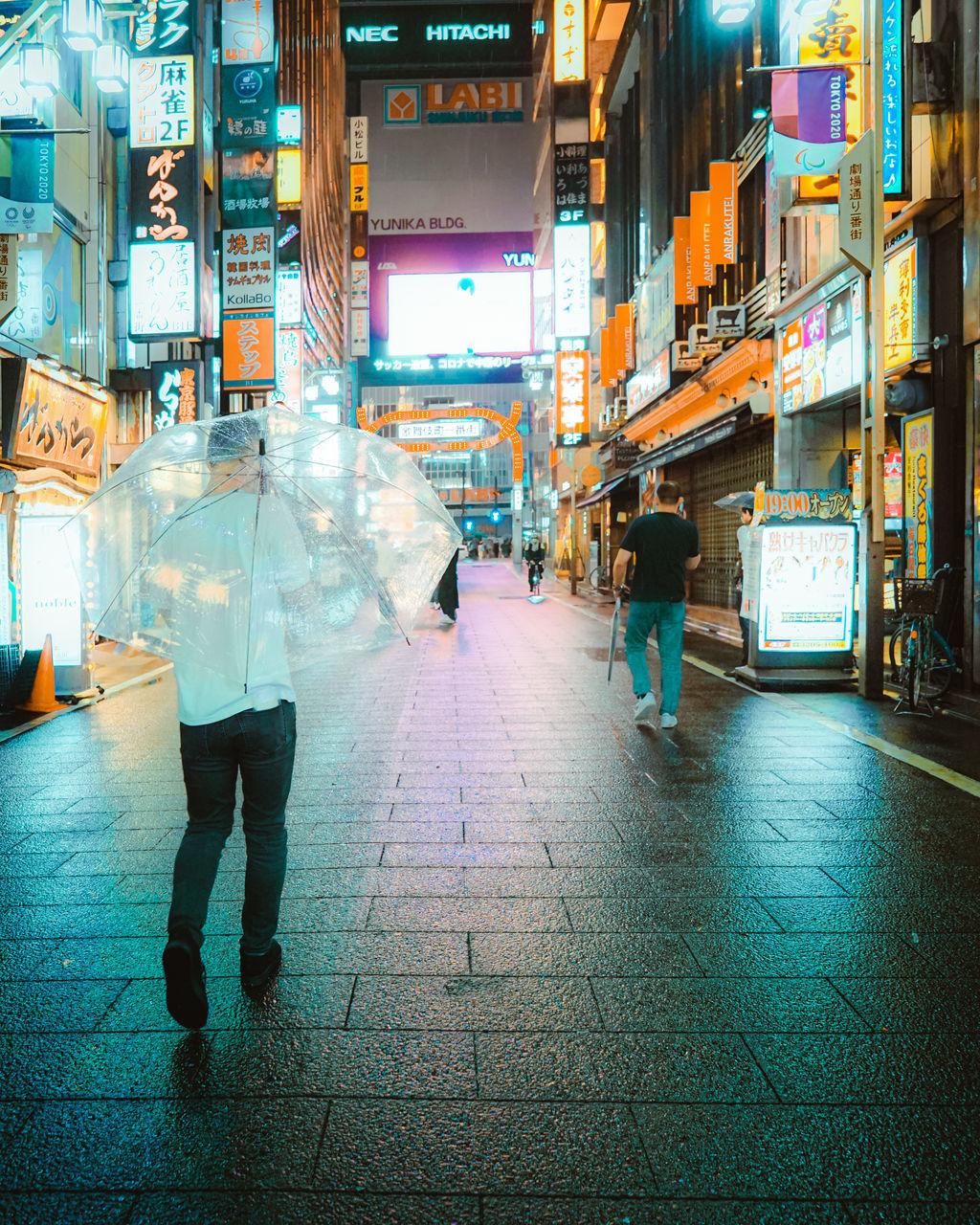 PEOPLE WALKING ON ILLUMINATED STREET