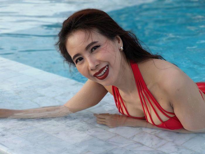 Portrait of smiling mature woman wearing bikini swimming in pool