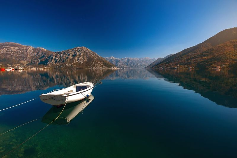 Boats moored on lake against clear blue sky
