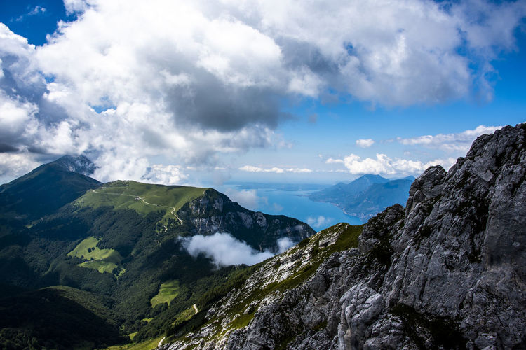 View of lake garda between rocks, clouds and blue sky on monte altissimo di nago in trento, italy