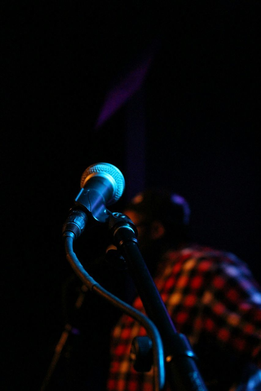 Close-Up Of Microphone With Musician In Background