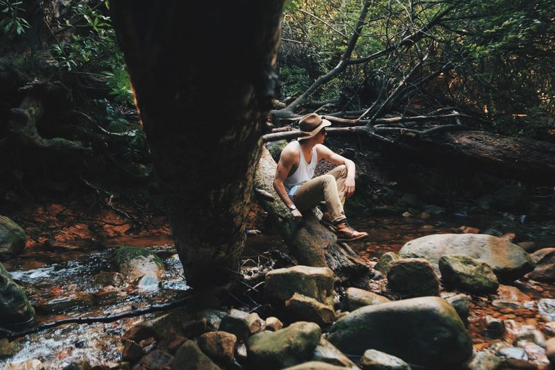 Man Sitting On Fallen Tree Over Stream In Forest