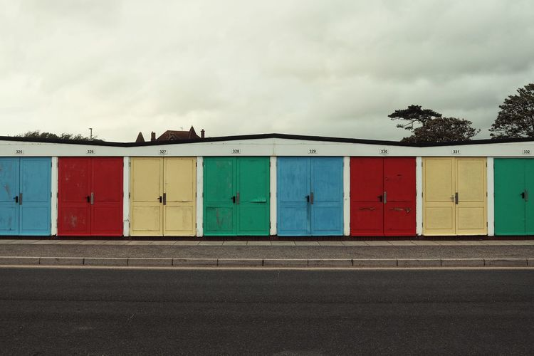 Multi colored building by road against sky