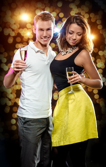Couple Holding Champagne Flutes While Standing At Party