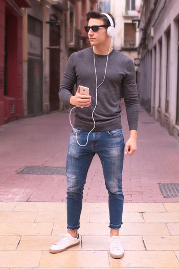 Full length of young man standing on footpath