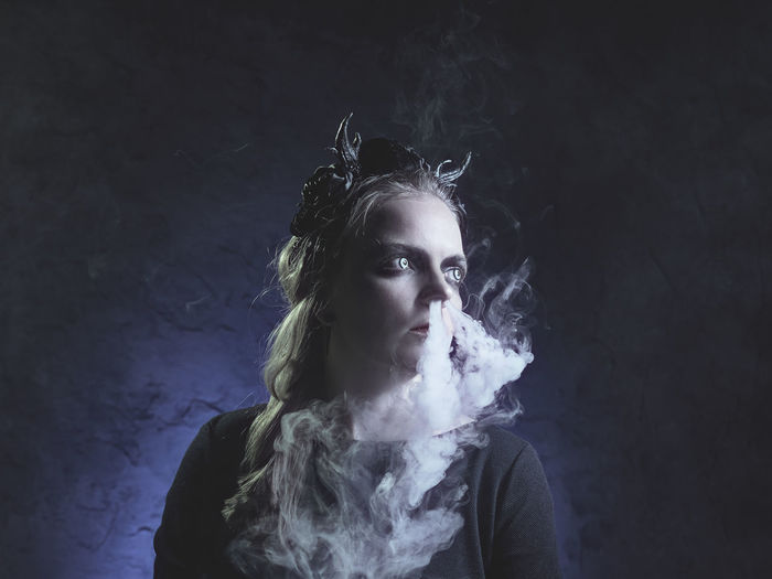 Spooky young woman emitting smoke from nose against black background