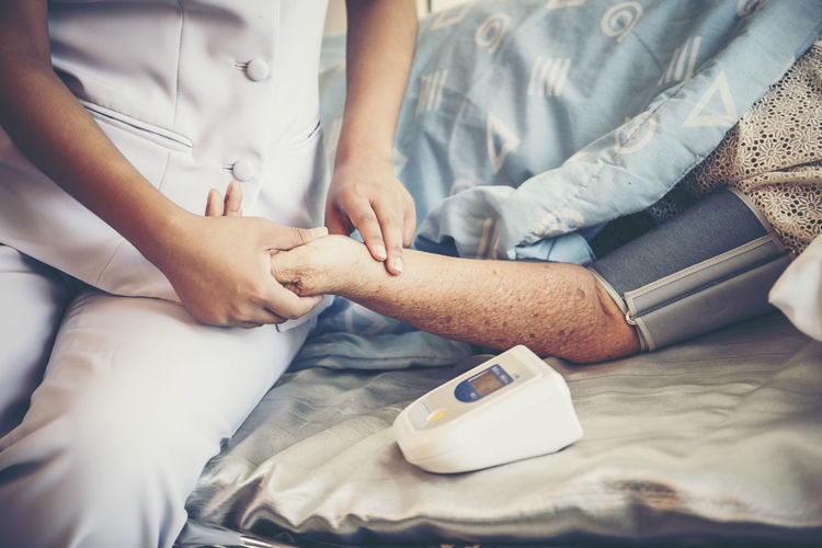 Midsection of nurse checking blood pressure of man at hospital