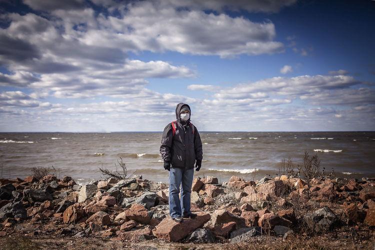 Full length of man standing on rock at beach against sky