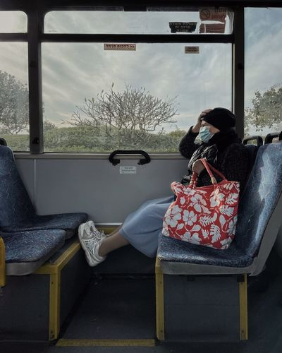 Rear view of man sitting on seat in bus