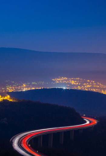 Illuminated Light Trail Night Transportation Sky Road Long Exposure Motion Nature No People Speed Blue Mountain Cloud - Sky City Red Blurred Motion Mode Of Transportation High Angle View Curve Outdoors