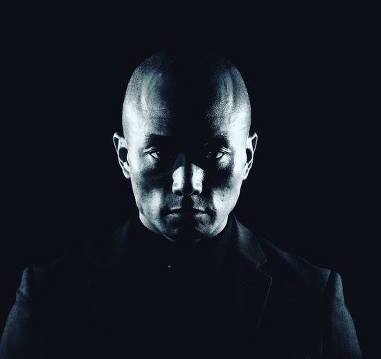 Low-key portrait of man against black background