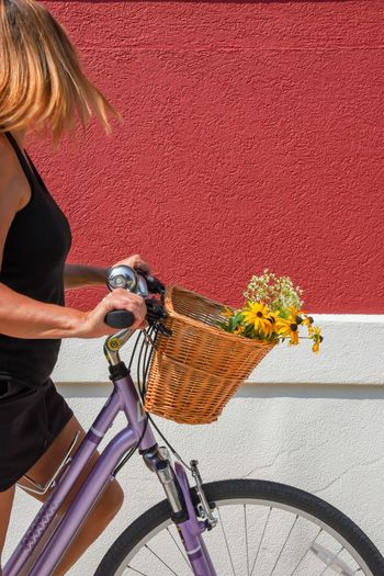 Midsection of woman riding bicycle on red wall