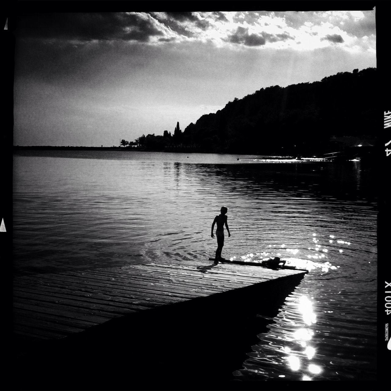 Boy on pier in lake